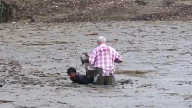 Heroic Thai fisherman valiantly puts himself at risk to help tourists stuck in mud