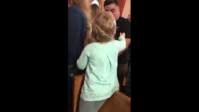 Adorable toddler stands on church pew to hug everyone on their way to communion