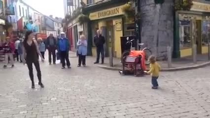 Adorable toddler sees a woman Irish dancing in the streets and decides to join in