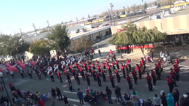 Marching band lines up in perfect unison, crowd erupts with laughter when song changes