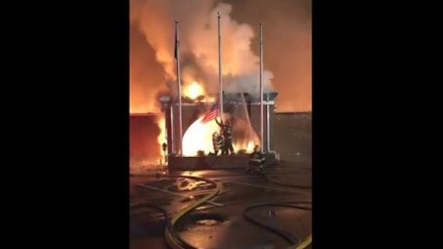 As building is destroyed by blaze, firefighters save American flag before it catches fire